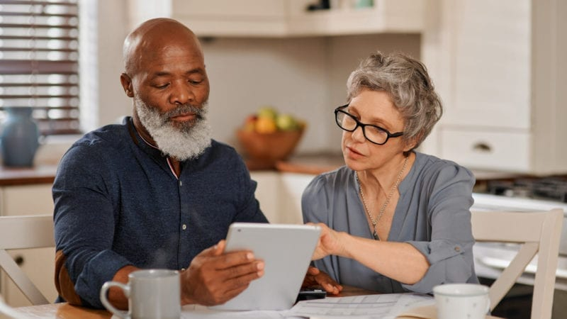 senior couple using a tablet to compare affordable cremations